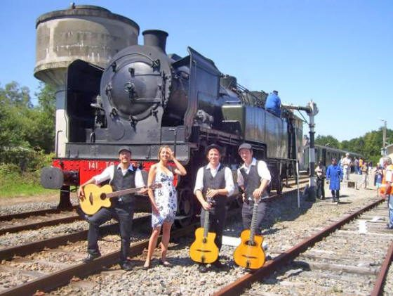 Le groupe Trio BBQ devant une locomotive