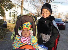 Un enfant dans un carrosse et au autre debout bien déguisés, prêts pour l'Halloween