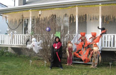 Enfant costumé devant une maison bien décorée