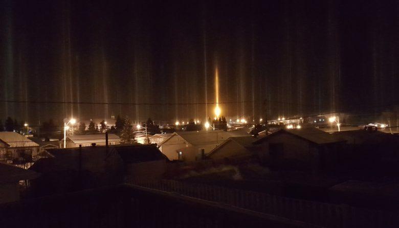 Trainées lumineuses au-dessus des maisons du village