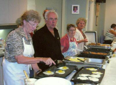 Des bénévoles qui préparent et servent le repas