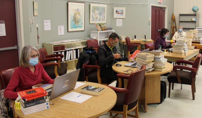 Bénévoles inscrivant les nouvelles données avec des ordinateurs...