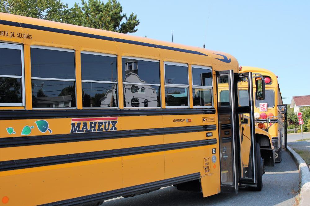 Autobus scolaire arrêté près d'une école à Évain.
