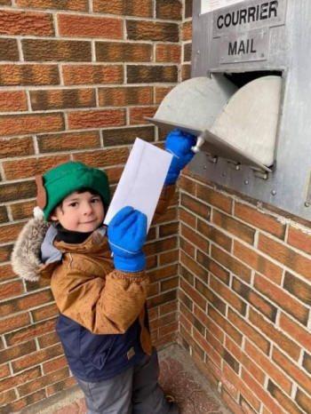 Un enfant dépose une lettre dans la boite de courrier.