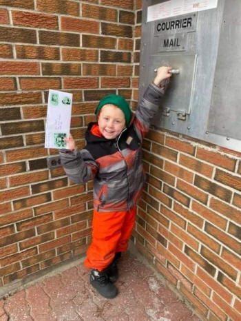 Un enfant souriant poste une carte au père Noël