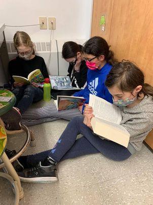4 jeunes filles assises dans un coin pour lire