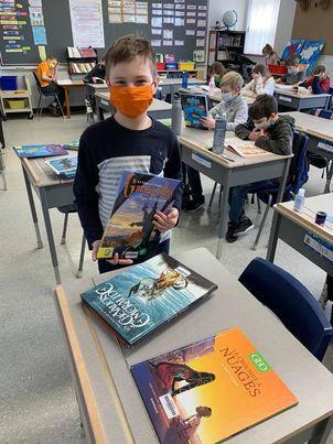 Un enfant choisit un livre parmi ceux sur la table
