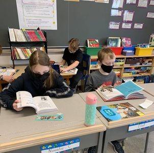 Trois étudiants feuilletant des livres